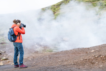 Reykjadalur, Iceland Hot Springs road footpath with steam fumarole vent during autumn day in golden circle with people woman girl taking picture photographing on hiking trail