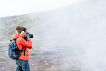 Reykjadalur, Iceland Hot Springs road footpath with steam fumarole vent during cold autumn day in golden circle with people woman girl taking picture photographing