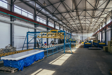 Modern thermal insulation sandwich panel production line. Machine tools, roller conveyor in workshop