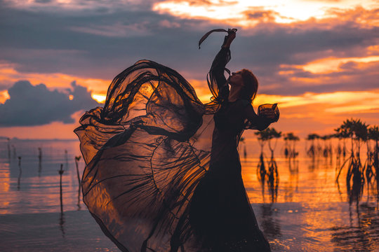 beautiful young woman dancing in water at sunset silhouette