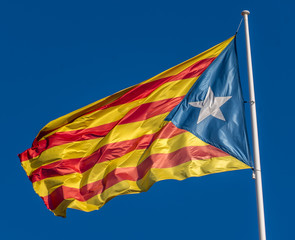 Catalan flag in support of the independence of Catalunya flies above Girona with blue sky background