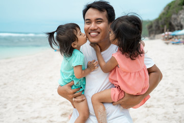 two little girl kissing together to his father on the beach