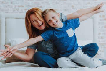 Happy mom and little son having fun at home