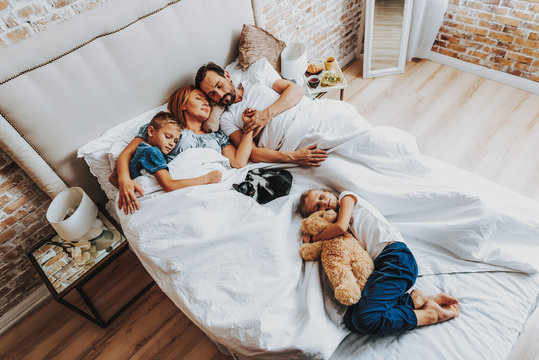 Top view of family sleeping together in bed
