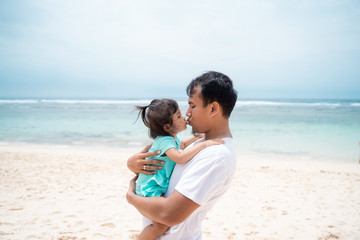 father and his daughter kissing each other on the beach