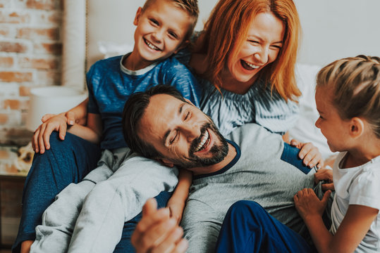 Happy parents and two kids laughing together