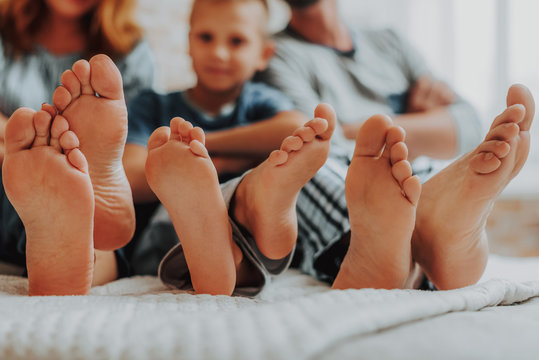 Close up family three pairs of feet in bed