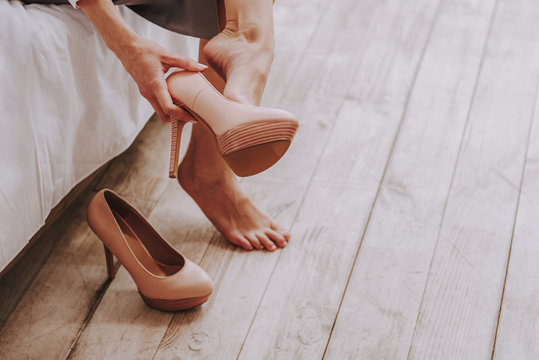 Frazzling young woman unshoes stilletos from feet at home