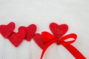 Valentines day decorative background with decorative red hearts with decorative ribbon on a white background. Close up. Top view.
