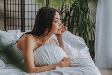 Beautiful young female dreaming in cozy bedroom