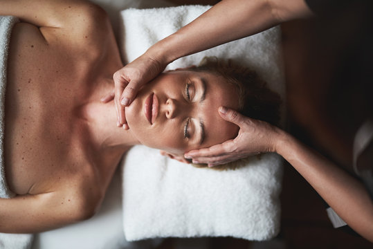 Top view of anti-age massage of face to lady