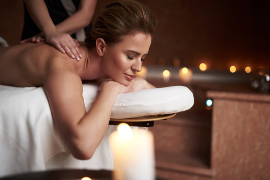 Relaxed young lady having massage in spa salon