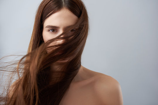 Young lady with hair strands on her face standing against light blue background