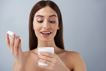 Cheerful young lady opening white jar of cosmetic cream