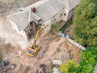 yellow excavator working at old building destruction. demolition site aerial top view