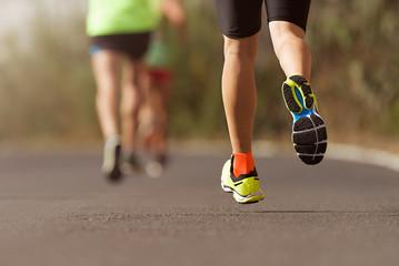 Runners feet running on road close up on shoe,  male triathlete runner
