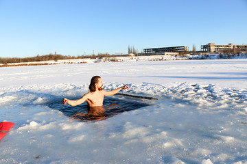 A young man is preparing to dive into the ice hole. Winter, cold, open water.