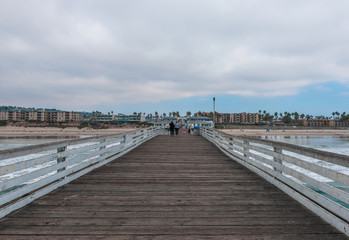 Wooden bridge to the ocean. Pacific Beach Pier or Crystal Pier.