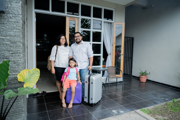 family with suitcase standing in front of their house