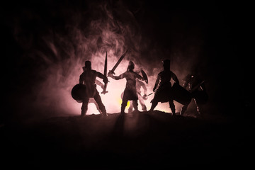 Medieval battle scene. Silhouettes of figures as separate objects, fight between warriors on dark toned foggy background. Night scene.