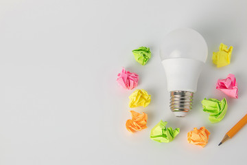 multi-colored sticky notes crumpled papers ball,Light bulb a pencil on white background office concept no idea