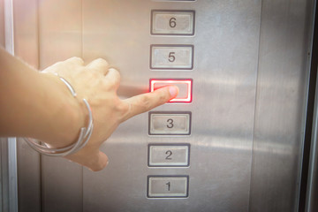 The hand presses on the fourth floor button in the elevator.