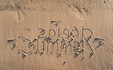 The inscription SUMMER 2019 is written on the sand. The drawing is made by hand. Postcard. Beach holidays.