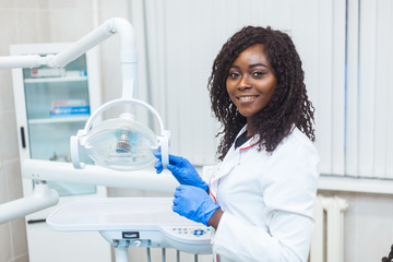Portrait of female black dentist in dental office. She standing at her office and she has beautiful smile.