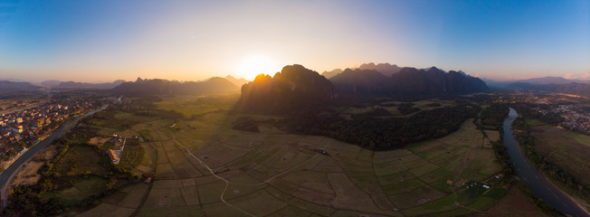 Aerial: Vang Vieng backpacker travel destination in Laos, Asia. Sunset over scenic cliffs and rock pinnacles, rice paddies valley, stunning landscape.