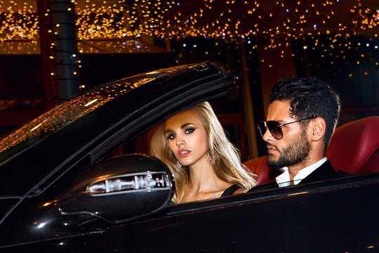 Couple in luxury car. Night life.