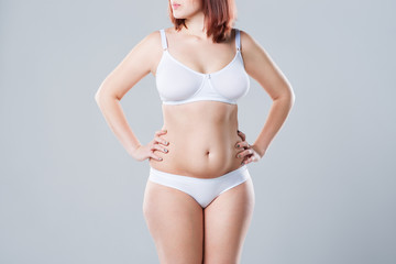 Woman with fat abdomen, overweight female body on gray background