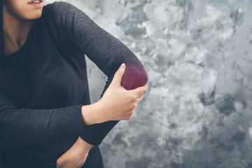 woman pain elbow on dark background