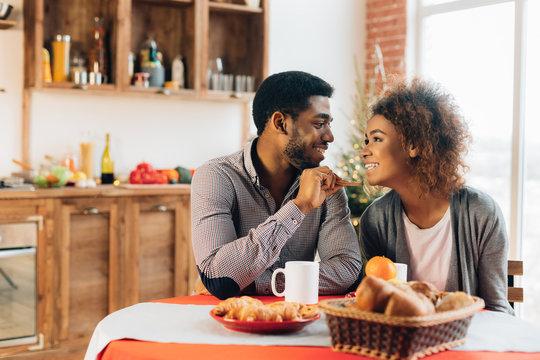 African-american couple enjoying tasty cookies in kitchen