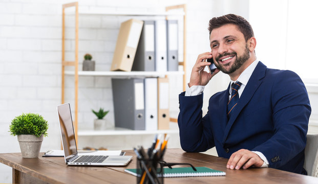 Good business talk. Man talking on phone and smiling