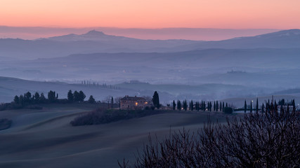 Beautiful sunrise on the Tuscan hills between San Quirico d'Orcia and the Rocca di Radicofani, Siena, Italy