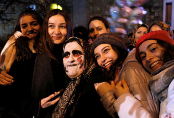 Participants pose with an elderly reveler wearing scary make up during the Bocuk night, or the Thracian Halloween, in Camlica village, near the western town of Kesan