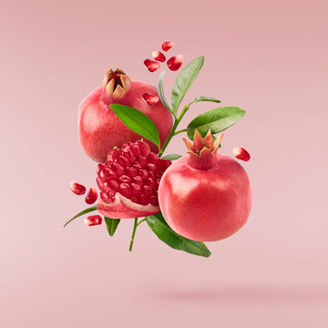 Flying in air fresh ripe whole and cut pomegranate with seeds and leaves