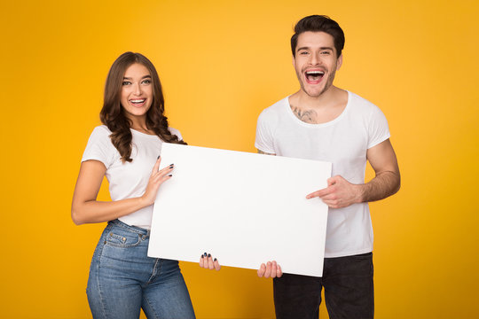 Happy couple holding white banner with copy space