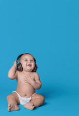 Cute laughing baby boy listening to music