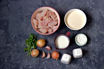 Ingredients for cooking homemade fish cakes: raw fish fillet, onion, garlic, milk, cornstarch, salt, pepper, breadcrumbs, parsley. Top view.
