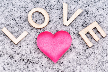 Drawing of a heart on the snowy .Valentine's Day. Heart of pink in the snow with the letters sweet. Valentine's Day. Soft focus. Background. Close-up.Heart drawn in the snow.