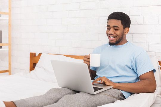 Businessman working on laptop with coffee in bed