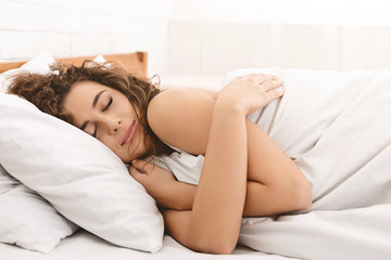 Gorgeous young woman hugging herself while sleeping