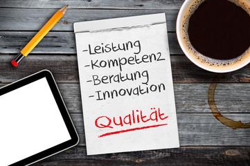 Notizblock auf Schreibtisch mit Leistung, Kompetenz, Beratung, Innovation und Qualität