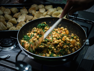 Hand stirring Indian chickpea and spinach curry in wok on gas stove indoors.