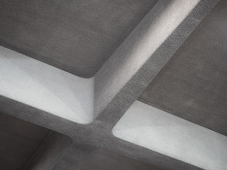 Low angle view of massive concrete crossbeam in form of cross on ceiling indoors.