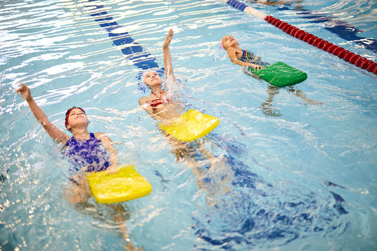 Children swimming backstroke with boards during lesson in swimming pool