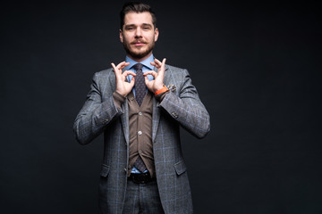 A confident elegant handsome young man standing in front of a black background in a studio wearing a nice suit.