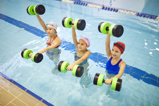 Group of little girls standing in the pool and exercising with dumbbells during aqua aerobics