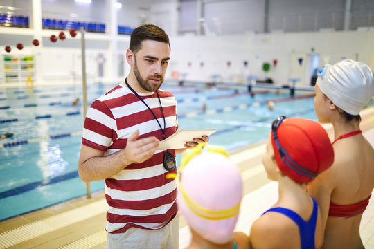 Young swim instructor standing with digital tablet and talking to the little girls before training in the swimming pool
